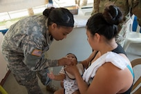 Specialist Gloria Galbearth, a U.S. Army Licensed Practical Nurse with the 139th Medical Brigade in Missouri, assists Guatemalan nurses with the inoculation of babies during a Medical Readiness Training Exercise (MEDRETE) at a health clinic in Flores, Peten, in Guatemala.