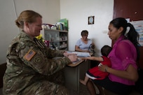 U.S. Army Maj. Adina Sanchez, a Nurse Practitioner with the 325th Combat Support Hospital  assists Guatemalan Dr. Jeanette Corzantes Barrios to evaluate patients during a Medical Readiness Training Exercise (MEDRETE) at a health clinic in Flores, Peten in Guatemala.