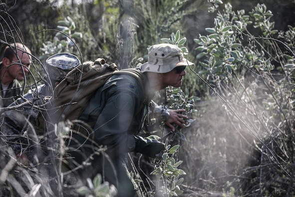 Lt. Col. Steven Shrader, 445th Operations Group deputy commander, takes cover during Evasion, Resistance and Escape (SERE) training at Naval Amphibious Base, Coronado, California, Jan. 20, 2019. Members of the 445th Airlift Wing Operations Group performed their annual training at Naval Amphibious Base, Coronado and Marine Corps Air Station Miramar near San Diego, California Jan. 18-27, 2019. The training included water survival, Survival, Evasion, Resistance and Evasion, and low altitude flying. (U.S. Air Force photo/Master Sgt. Patrick O'Reilly)