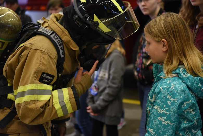 Airman 1st Class Kayla Jerido, 86th Civil Engineer Squadron firefighter shows Lucena Hanna her fire protection gear during Young Women in Aviation Day on Ramstein Air Base, Germany, March, 9, 2019. Jerido showed how fast she could put on her suit and equipment, while also showing the many instruments that protect her during a fire.