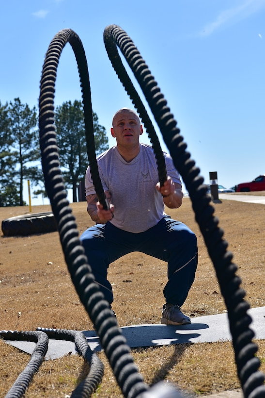 An Airman wings battle ropes while outside