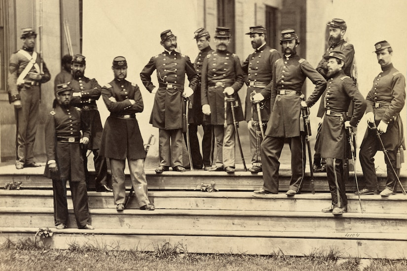 Soldiers stand in front of a mansion.