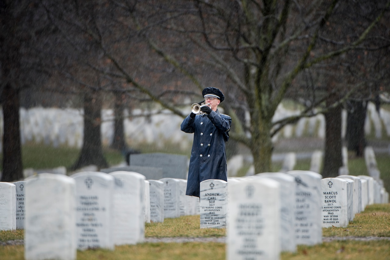 A trumpeter plays in a cemetery.