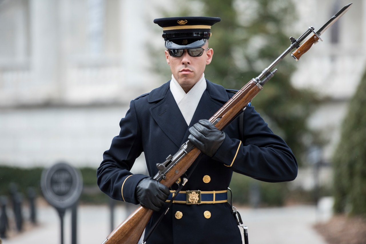 A soldier in dress uniform and sunglasses holds a rifle.