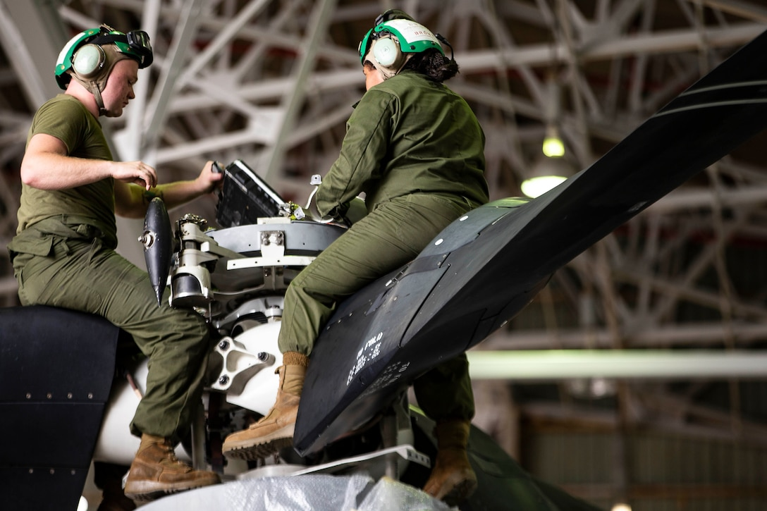 Two Marines work on a helicopter while sitting on it's wings.
