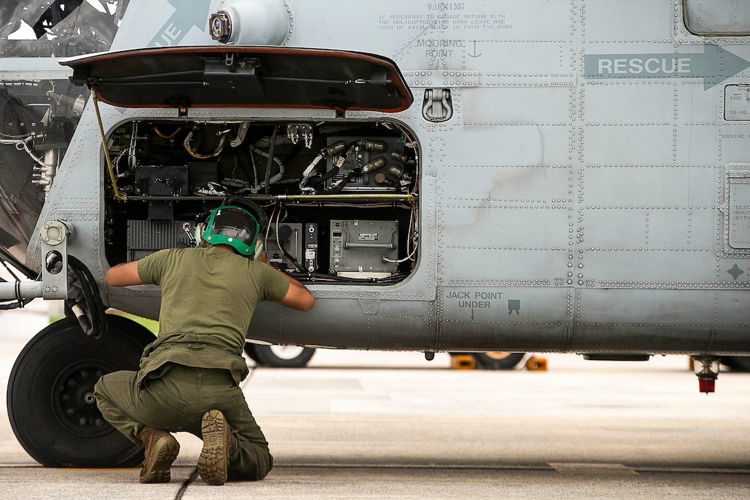 A Marine knelt down working on an aircraft.