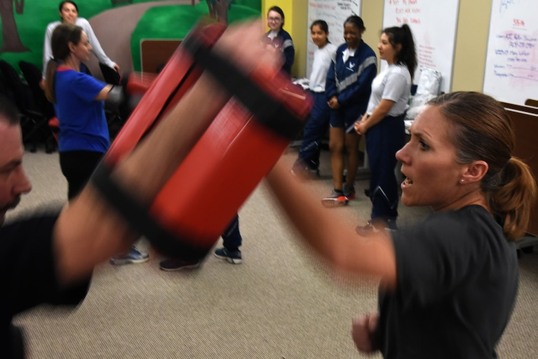RaNay Conrow, an Air Force dependent, practices blocking an aggressor, which for training purposes is an arm pad, during a women's self-defense class in the Goodfellow Resiliency Center, at Goodfellow Air Force Base, Texas, March 8, 2019. Fifteen women attended the event. (U.S. Air Force photo by Airman 1st Class Abbey Rieves/ Released)