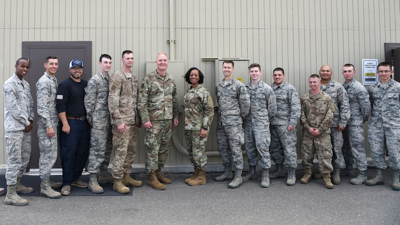U.S. Air Force Col. Michael Hough, 30th Space Wing commander, and Chief Master Sgt. Diena Mosely, 30th Space Wing command chief, take a group photo with the 12 30th Civil Engineer Squadron Airmen March 12, 2019, at Vandenberg Air Force Base, Calif. Hough and Mosely both presented their coins to the Airmen for their tedious and tireless work when a storm hit Vandenberg AFB, March 8, 2019.