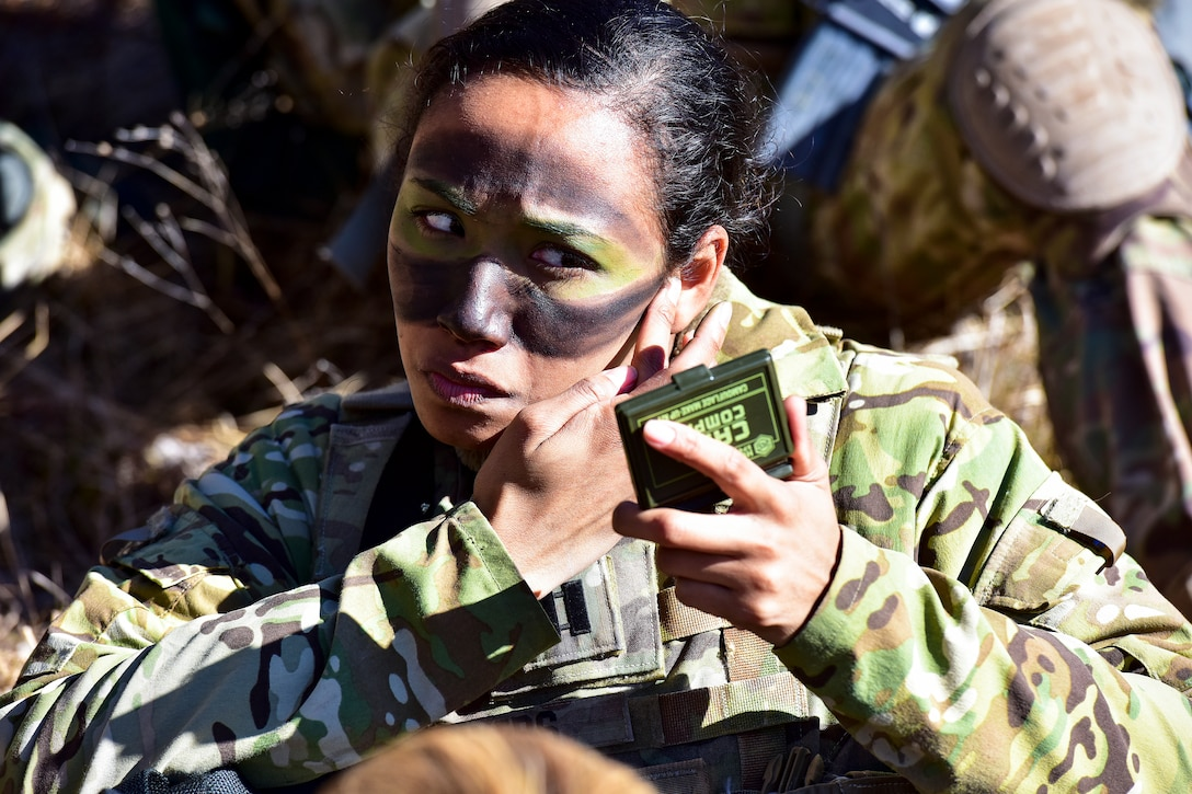 A soldier paints her face green and black while holding a small mirror.