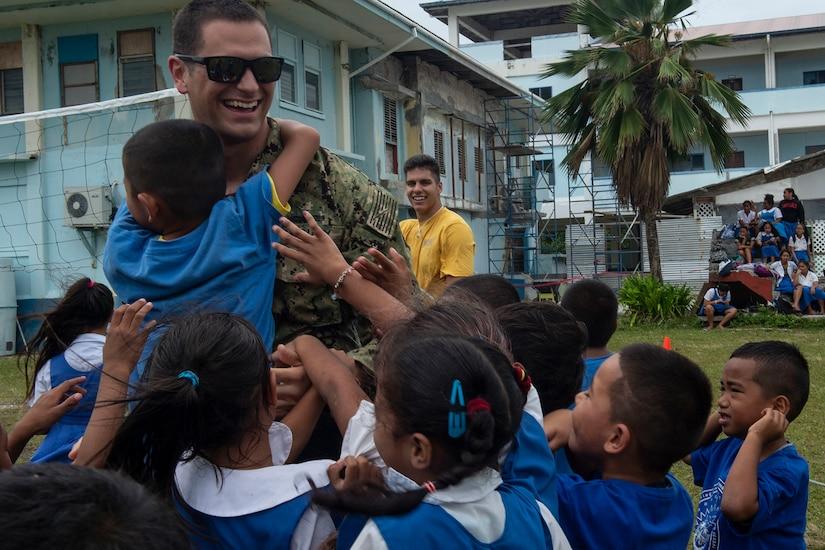 A service member interacts with students.
