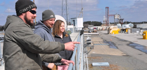 "IMAGE: DAHLGREN, Va. (March 4, 2019) - Jennifer Ferrell - administrative lead for the Test and Evaluation Division at Naval Surface Warfare Center Dahlgren Division (NSWCDD) - looks out over the Potomac River Test Range (PRTR) as Chris Hayden, left, and Richard Lay explain their responsibilities as PRTR gun captains - to maintain, sustain, and ensure the safe operation of all Gun Weapon Systems on the range. The gun captains are key members of the Range Safety Team during range test execution involving guns, electric weapons, and unmanned systems. ""The faster we can get funds properly in place, the faster we can execute the technical work to get the products delivered to the warfighter,"" said Ferrell who is responsible for the financial and human resources actions and financial management of PRTR. ""I find pride in knowing that even though my role is non-technical, I can still make an impact to our warfighters by promoting more efficient financial and human resources policies and processes."""