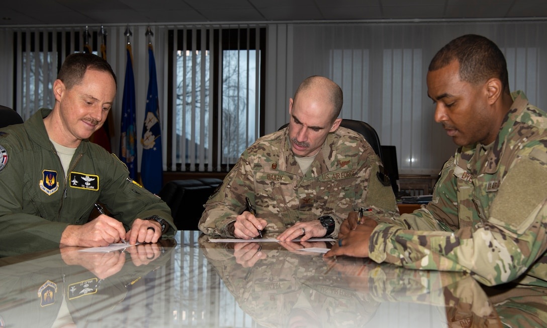 U.S. Air Force Col. Jason Bailey, 52nd Fighter Wing commander, center, Col. Tad Clark, 52nd FW vice commander, left, and Chief Master Sgt. Alvin Dyer, 52nd FW command chief, right, donate to the Air Force Assistance Fund at Spangdahlem Air Base, Germany, March 13, 2019. The AFAF includes four charities that provide support to Airmen and retiree's widowed spouses in need. (U.S. Air Force photo by Airman 1st Class Valerie Seelye)