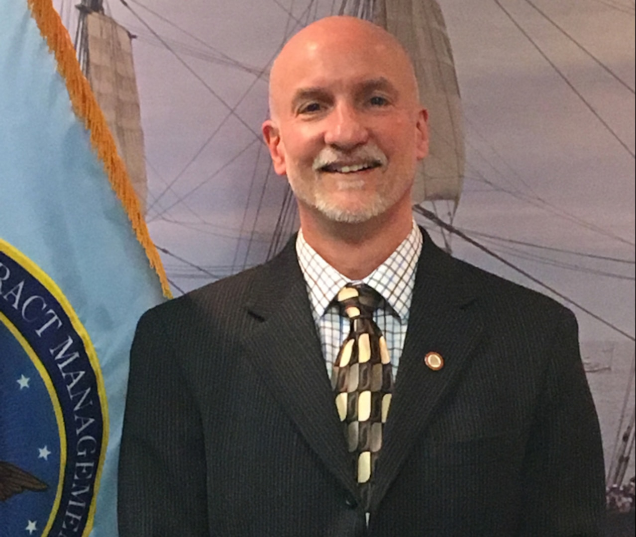 Smiling man wears a dark suit and stands by the DCMA flag