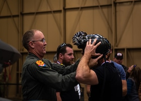 Brig. Gen. Todd Canterbury, 56th Fighter Wing commander, places his F-35A Lightning II helmet on an Airpower Foundation member during a base tour, March 8, 2019 at Luke Air Force Base, Ariz.