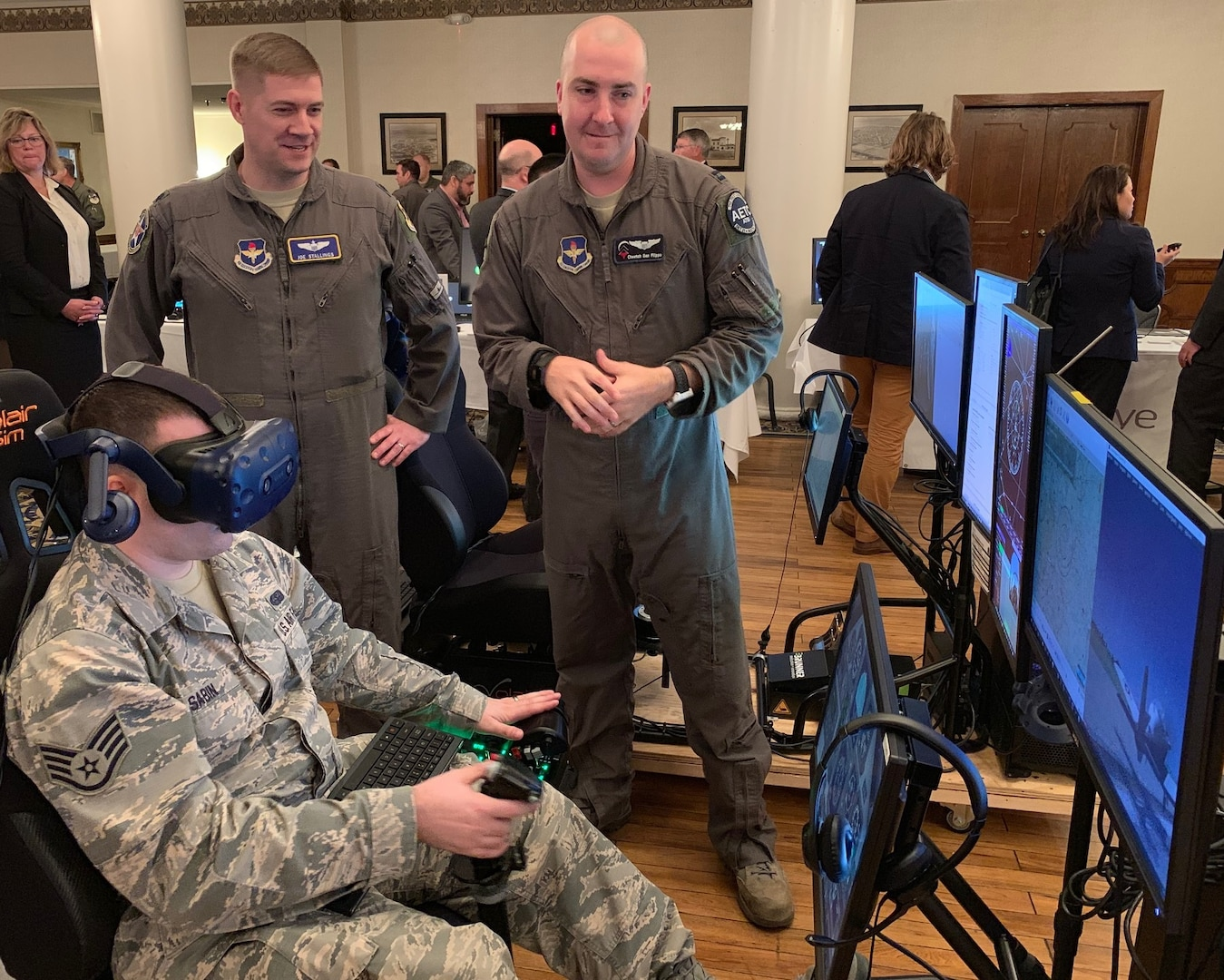 Lt. Col. Joe Stallings (left), 12th Flying Training Wing Innovation Director, and Capt. Calogero San Filippo (right), Pilot Training Next instructor pilot, discuss virtual-reality flying technology while Staff Sgt. Joseph Sabin, Air Education and Training Command Technology Integration Detachment, flies a VR sortie at the PTN Technology Expo at Joint Base San Antonio-Randolph March 12. Flying training wings will formally begin integrating innovations from PTN into the undergraduate pilot training curriculum beginning May 31, 2019.