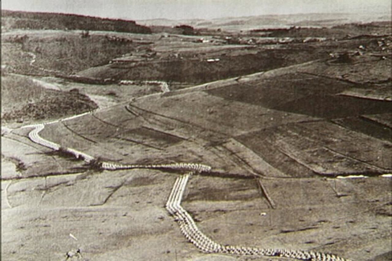 A black-and-white photo of a German hillside  covered with a line of defenses .