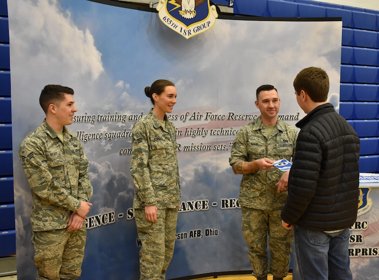 655th Intelligence, Surveillance, and Reconnaissance Wing, 71st Intelligence Squadron analyst Senior Airman Roark hands a senior class student an information brochure at Xenia High School, Xenia, Ohio, March 13, 2019.  Roark and other members of the 71st and 14th intelligence squadrons participated in a career day held at the school to promote the 655th mission, as well as the opportunities and benefits available in the United States Air Force Reserve.  The event was sponsored by the Ohio Means Jobs Greene County office.