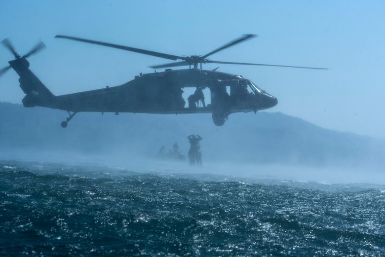 Service members practice helocasting by jumping into a lake from a UH-60 Blackhawk at Lake Ilopango, El Salvador, March 7, 2019.