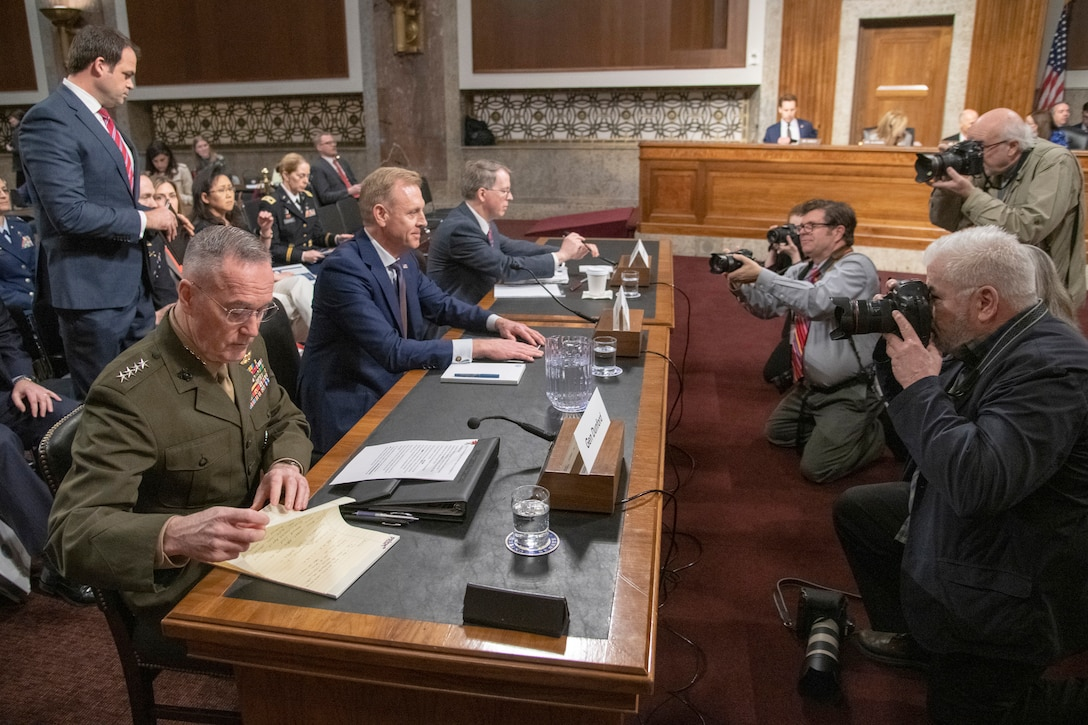 Photographers take pictures of Marine Corps Gen. Joe Dunford, Acting Defense Secretary Patrick M. Shanahan and David L. Norquist at a table.