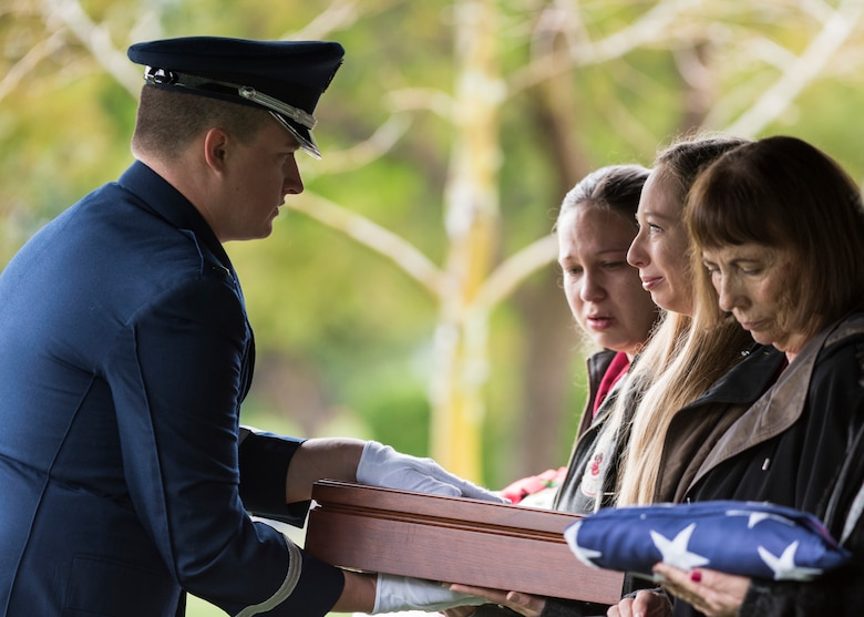 1st Lt. Andrew Forsythe, Honor Guard officer in charge, presents a flag to a family member of the deceased during a U.S. Air Force active duty funeral March 2, 2019, in Camarillo, Calif. According to the United States Department of Veteran Affairs, a military burial flag is provided to a deceased veteran in order to honor the memory of his service to the country. (U.S. Air Force photo by Airman 1st Class Aubree Milks)