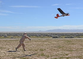 A man hand launches a small airplane.
