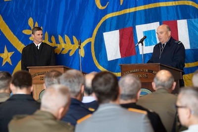 Two NATO military officers discuss naval operations.