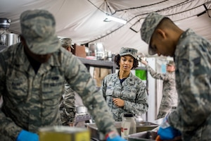 Lt. Col. Joy Atkins, 512th Memorial Affairs Squadron commander, observes the 512th MAS cooking team as they prepare food during the John L. Hennessy food service competition at Dobbins Air Reserve Base, Georgia, March 9, 2019. The 512th MAS cooking team were tasked with serving an appetizer, three entrées and dessert as a part of the competition rules. (U.S. Air Force photo by Staff Sgt. Damien Taylor)