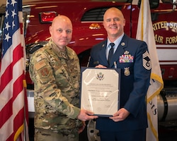 Col. Reid gives Chief Otto his retirement certificate.