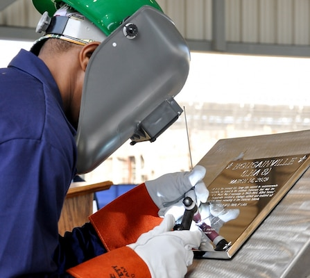 Ingalls Shipbuilding welder Cedric Harman welds Ship Sponsor Ellyn Dunford's initials into a steel plate during the keel authentication ceremony of the future USS Bougainville (LHA 8) at Huntington Ingalls Industries Pascagoula shipyard March 14.
