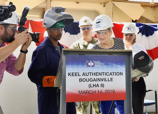 Ship Sponsor Ellyn Dunford traces her initials before Ingalls Shipbuilding welder Cedric Harman welds them into a steel plate to be fastened to the ship during the keel authentication ceremony of the future USS Bougainville (LHA 8) at Huntington Ingalls Industries Pascagoula shipyard March 14.