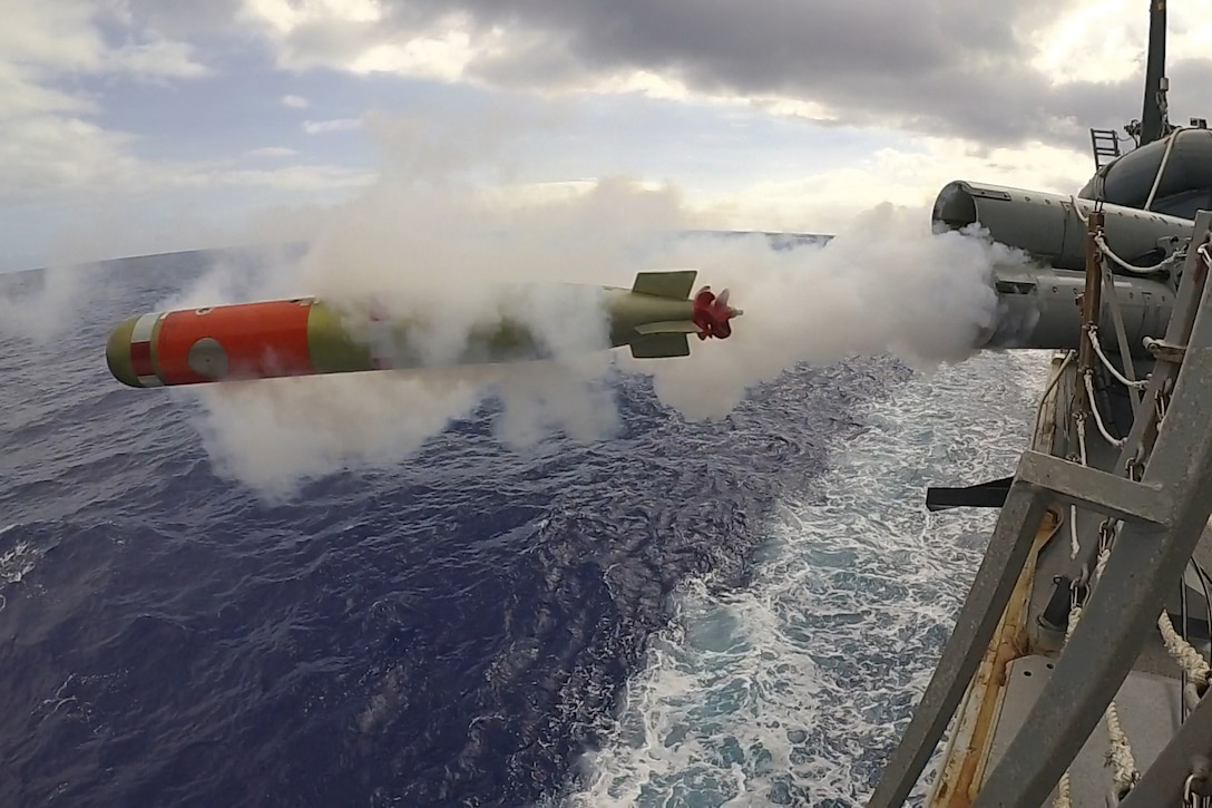A torpedo launches from a military ship.