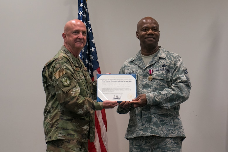 Col. Jay Johnson, 403rd Maintenance Group commander, presents Chief Master Sgt. Michael Herbert, 403rd Aircraft Maintenance Squadron superintendent, with his Appreciation Certificate for his military service during his retirement ceremony held at the Roberts Maintenance Facility March 9. (U.S. Air Force photo by Staff Sgt. Shelton Sherrill)