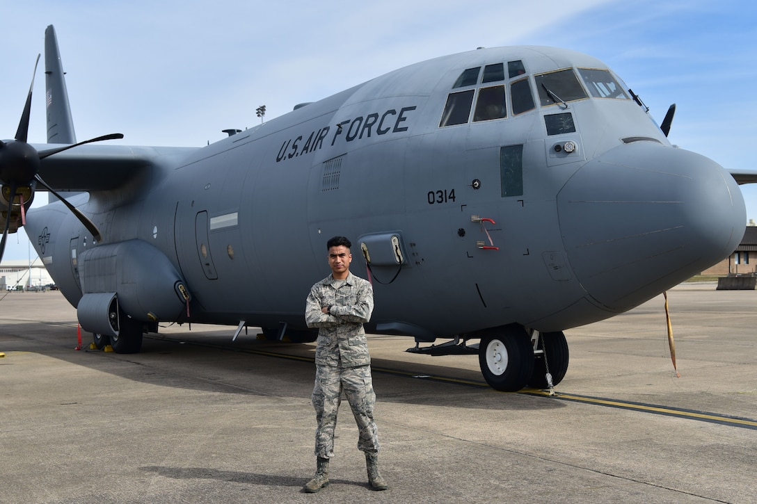 Airman poses in fron of a C-130J.