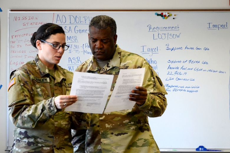Sgt. 1st Class Sarah Stanley and Staff Sgt. Alton Crosslin discuss the statement of work for the request to support the Federal Emergency Management Agency's operations after a mock hurricane hit the coast of Florida during the Logistics Support Battalion Mobilization Exercise (MOBEX).