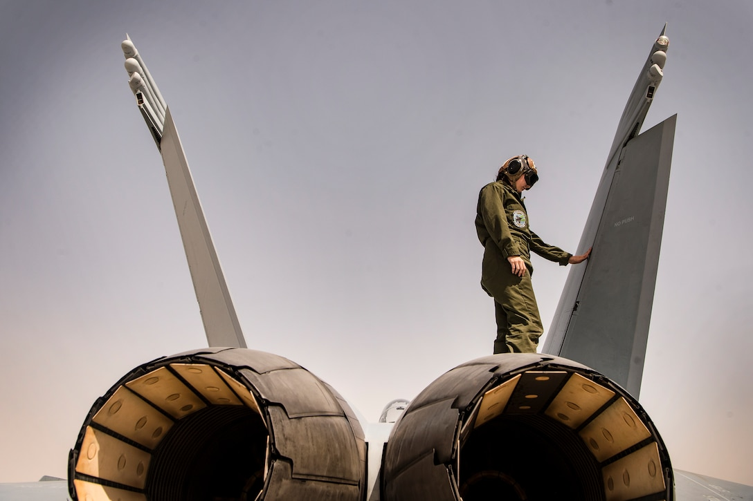 A sailor stands on top of a jet.