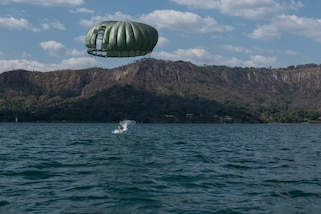 A service member lands into Lake Ilopango, El Salvador, after parachuting down from a UH-60 Blackhawk, March 5, 2019.