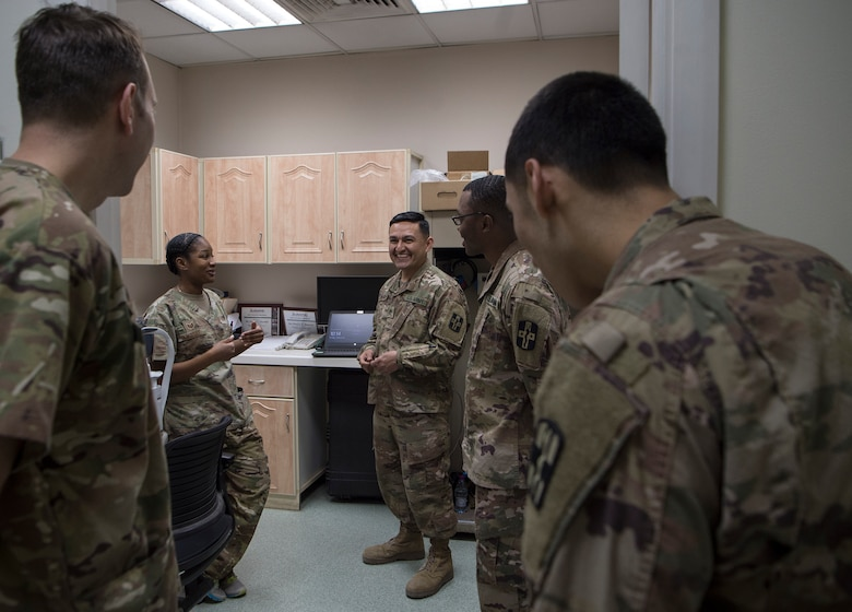 U.S. Air Force Tech. Sgt. Marquita Moore, center left, 379th Expeditionary Medical Group (EMDG) optometry NCO in charge and U.S. Air Force Lt. Col. Peter Carra, left, 379th EMDG optometry officer in charge from Al Udeid Air Base (AUAB), Qatar, talk with U.S. Army optical laboratory specialists of Area Support Group - Qatar (ASG-QA) from Camp As Sayliyah (CAS), Qatar, prior to a patient appointment March 9, 2019, at CAS. Moore and Carra travel to CAS once a week to provide eye care for Soldiers who, in turn, fabricate glasses prescribed for Airmen at AUAB and servicemembers at other deployed locations throughout U.S. Central Command.  (U.S. Air Force photo by Tech. Sgt. Christopher Hubenthal)