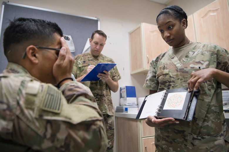 U.S. Air Force Tech. Sgt. Marquita Moore, right, 379th Expeditionary Medical Group (EMDG) optometry NCO in charge from Al Udeid Air Base (AUAB), Qatar, conducts an eye exam for a U.S. Army Soldier as U.S. Air Force Lt. Col. Peter Carra, 379th EMDG optometry officer in charge, documents data March 9, 2019, at Camp As Sayliyah (CAS), Qatar. Moore and Carra travel to CAS once a week to provide eye care for Soldiers who, in turn, fabricate glasses prescribed for Airmen at AUAB and servicemembers at other deployed locations throughout U.S. Central Command.  (U.S. Air Force photo by Tech. Sgt. Christopher Hubenthal)