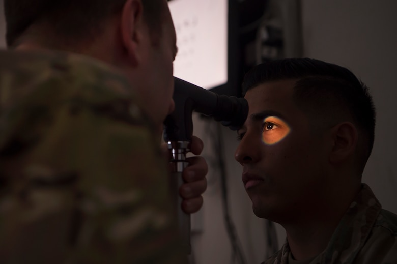 U.S. Air Force Lt. Col. Peter Carra, 379th Expeditionary Medical Group (EMDG) optometry officer in charge, performs an eye exam for a U.S. Soldier March 9, 2019, at Camp As Sayliyah (CAS), Qatar. Carra and Tech. Sgt. Marquita Moore, 379th EMDG optometry NCO in charge, travel to CAS once a week to provide eye care for Soldiers who, in turn, fabricate glasses prescribed for Airmen at Al Udeid Air Base, Qatar, and servicemembers at other deployed locations throughout U.S. Central Command.  (U.S. Air Force photo by Tech. Sgt. Christopher Hubenthal)