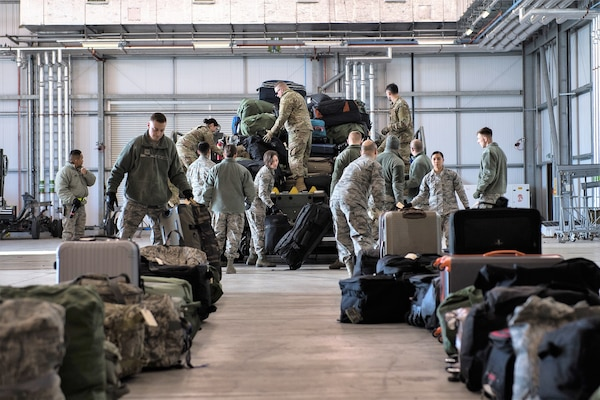 Airmen deployed from Barksdale Air Force Base, La., unload baggage at RAF Fairford, England, March 11, 2019. The Airmen deployed to support U.S. Strategic Command's Bomber Task Force (BTF) in Europe which validates the readiness and capability of the command.