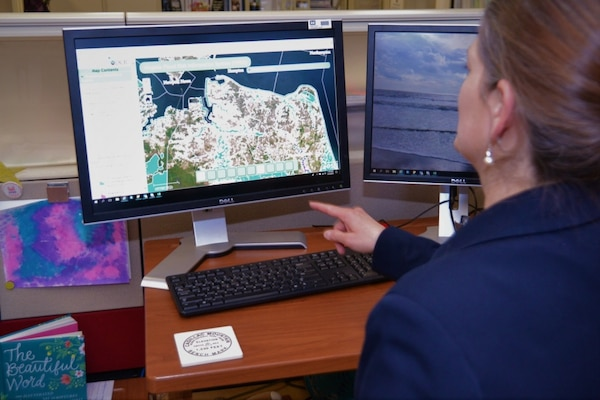 Woman in blue jacket points to a computer showing flood areas in Virginia