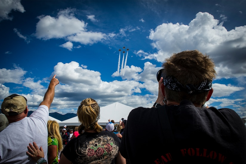 A crowd points toward the sky, where four F-16 Fighting Falcons are flying in a diamond formation.