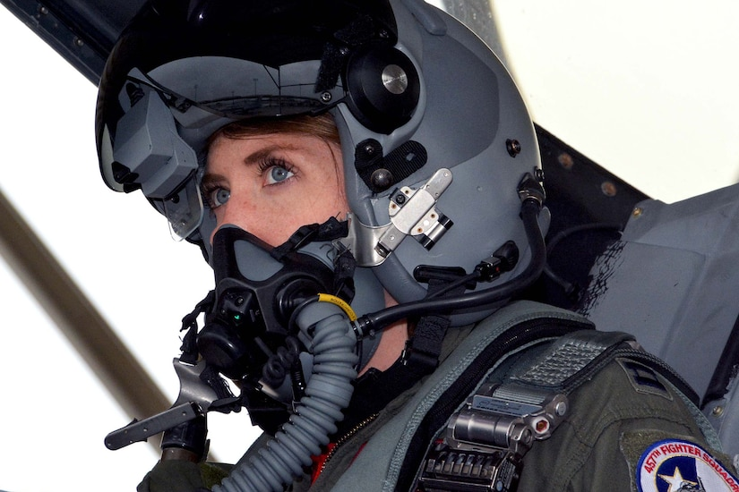 Close-up of a female pilot with helmet on sitting inside an F-16 Fighting Falcon.