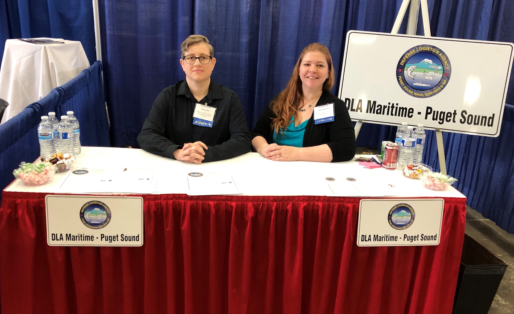 Two female associates sitting behind a booth.
