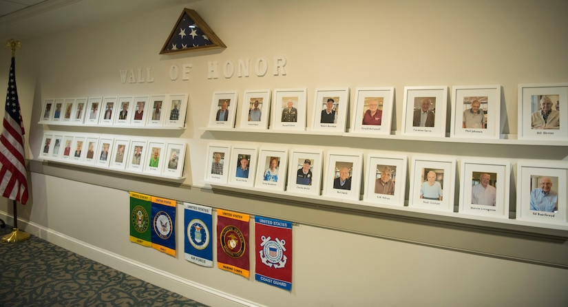 Vietnam, World War II and military veterans' photos line the wall at the Somerby of Mount Pleasant, a senior living community, as a display honoring Navy Week in Charleston, S.C.