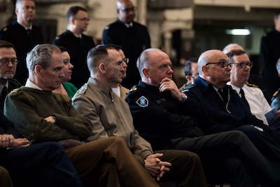 NATO military officers listen to speech.