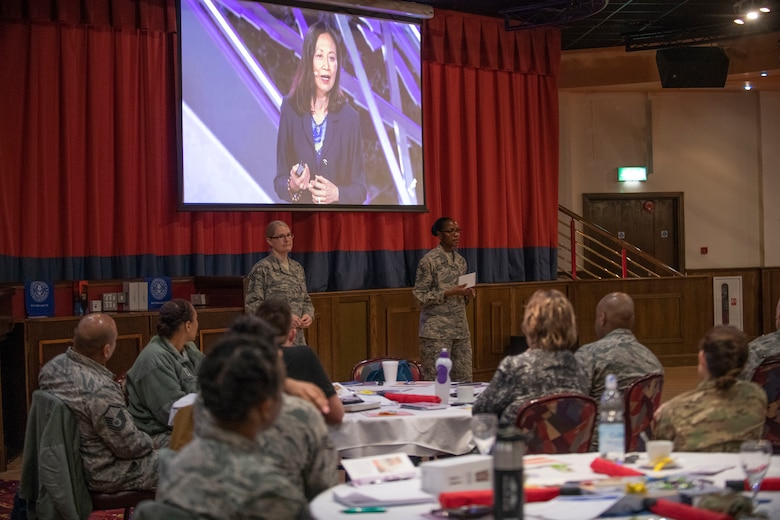 U.S. Air Force Chief Master Sgt. Tracy Wallace, 100th Force Support Squadron superintendent, and U.S. Air Force Senior Master Sgt. Angela Richardson, 100th Force Support Squadron lodging superintendent, speak to Airmen at RAF Mildenhall, England, March 14, 2019. The theme of this year's event was women leaders and included CEOs, human rights activists and motivational speakers. (U.S. Air Force photo by Senior Airman Luke Milano)