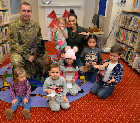 Retired Military Working Dog Vvonya enjoys a story with Ava Mort, 1, and Kimberly Mort, wife of Master Sgt. Joshua Mort, Team Mildenhall member, at the story and craft event at the base library on RAF Mildenhall, England, March 13, 2019. Children had the opportunity to make crafts, pet Vvonya and watch a military working dog demonstration at the event celebrating K9 Veterans' Day. (U.S. Air Force photo by Karen Abeyasekere)