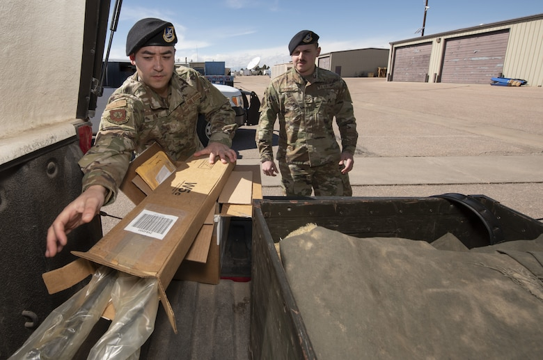 Staff Sgt. Garrett Brew, 50th Security Forces Squadron combat arms instructor, loads a shipment of rifle barrels into a truck as Senior Airman Austin Hopper, 50th Security Force Squadron resource and logistics, looks on at the 50th Security Forces logistics facility at Schriever Air Force Base, Colorado, March 11, 2019. The logistics flight is responsible for acquiring the equipment defenders need for carrying out their mission every day. (U.S. Air Force Photo by Staff Sgt. Matthew Coleman-Foster)