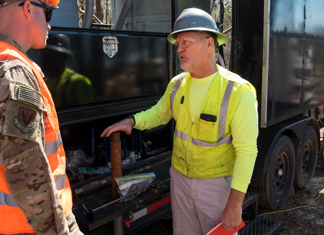 U.S. Air Force Maj. Brandon Goebel, 20th Civil Engineer Squadron commander, left, and Gary Simpson, AST Environmental project manager, discuss how the Enhanced Environmental Cleanup Technology, BOS 100® Treatment Barrier is injected at Sans Souci Farm in Sumter, S.C., March 7, 2019.